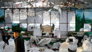 Les employés d'une salle de mariage inspectent les dégâts après une explosion à Kaboul, le 18août2019.