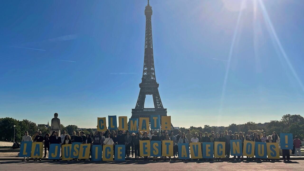"""Climate activists hold up posters to form a message that says """"Climate: justice is with us"""" as they celebrate the ruling of a court ordering the French state to order to fulfill its climate commitments, in front of the Eiffel Tower, in Paris, France, on October 14, 2021."""