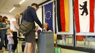 Odd ANDERSEN / AFP | Voters cast their ballots at a polling station in Berlin as in background can be seen the flags of Europe (L), of Germany (C) and of Berlin (R) during a regional election on September 18, 2016 in Berlin.