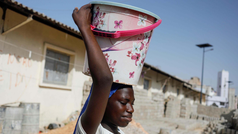Una joven carga un balde con agua potable en Pikine, en los suburbios de Dakar, Senegal, el 9 de marzo de 2020.