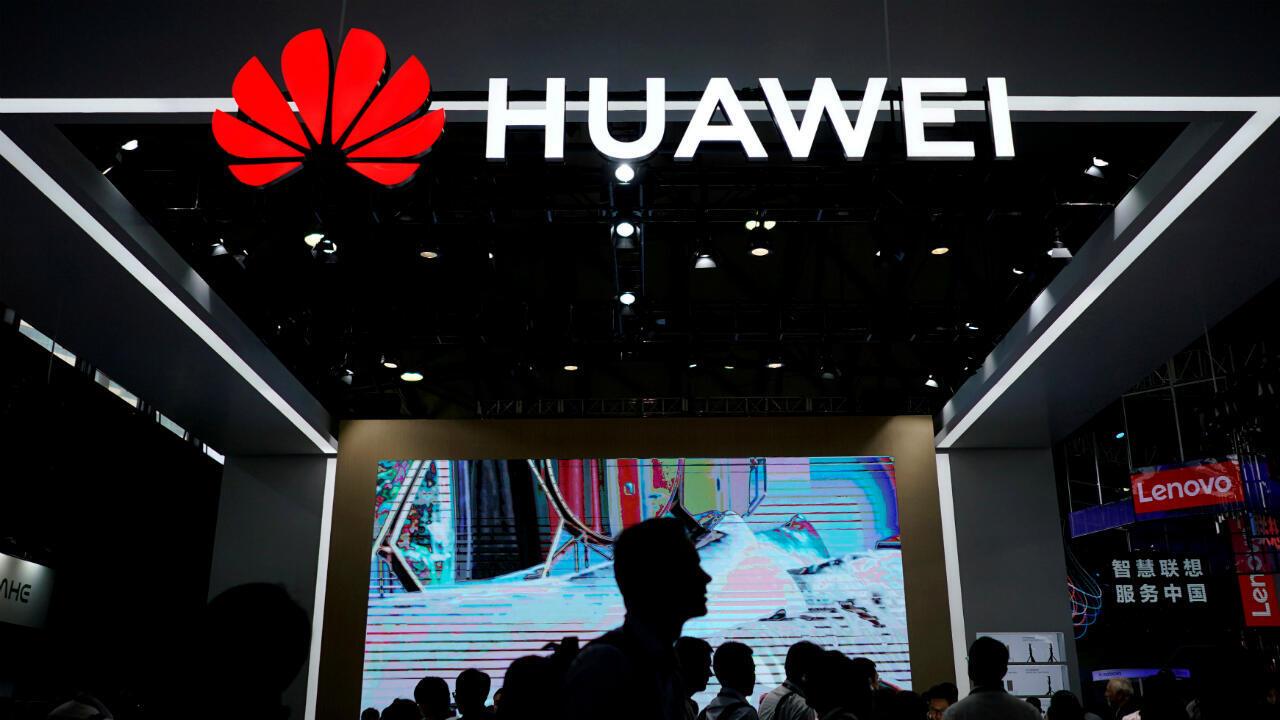 Des personnes passent devant un logo Huawei à Shanghai, en Chine, le 14 juin 2018.