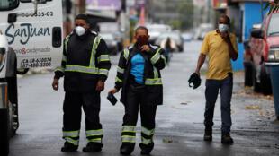 Empleados municipales revisan el estado de una calle el jueves 30 de julio de 2020, tras el paso de la tormenta tropical Isaías, en San Juan, Puerto Rico.