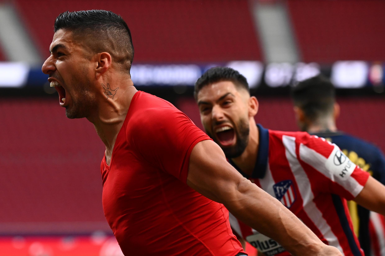Late joy: Luis Suarez celebrates the late winner that preserved Atletico Madrid's Liga lead