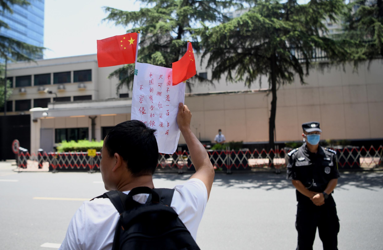 """Un hombre sostiene una pancarta y grita """"el Gobierno chino es increíble"""", fuera del consulado de Estados Unidos en Chengdu, provincia de Sichuan, suroeste de China, el 27 de julio de 2020."""