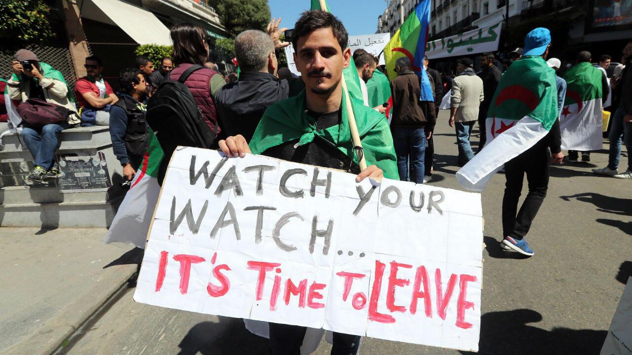 """Un joven en Argel sujeta un cartel con el mensaje """"Mira tu reloj, es hora de marcharse"""" durante la manifestación del 29 de marzo."""