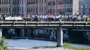 Familiares y amigos de las víctimas lanzan 43 rosas al río en memoria de las víctimas del colapso del puente Morandi, en Génova, Italia, hace un año