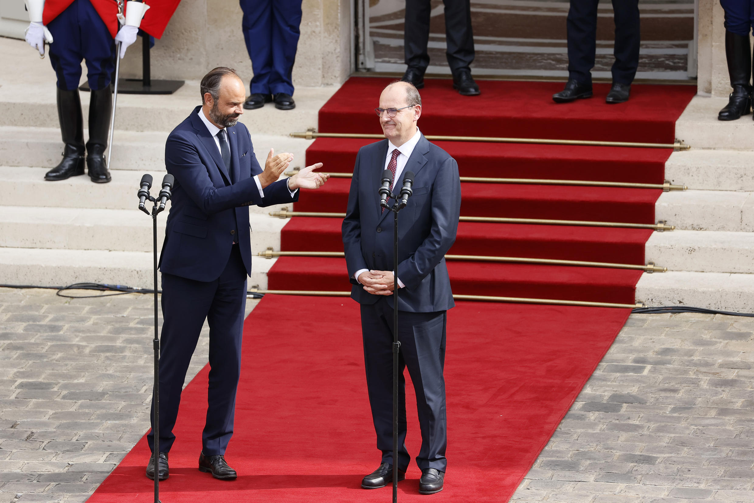 Former Prime Minister Édouard Philippe applauds his successor, Jean Castex, in the courtyard of the Hotel Matignon, July 3, 2020.