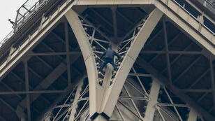 L'homme vêtu de noir suspendu aux barreaux de la tour Eiffel, le 20 mai 2019.