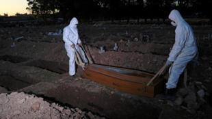 Trabajadores del cementerio que llevan indumentaria de protección, sepultan a una víctima del COVID-19 en el cementerio de Sao Franciso Xavier en Rio de Janeiro, el 29 de mayo de 2020