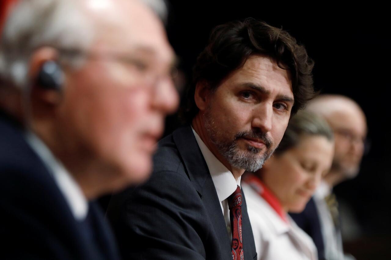 El primer ministro de Canadá, Justin Trudeau, escucha al ministro de Seguridad Pública, Bill Blair, durante una conferencia de prensa en Parliament Hill en Ottawa, Ontario, el 1 de mayo de 2020.