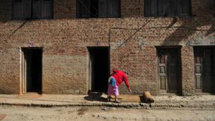 Une vieille dame déplie un matelas de paille en face de chez elle, à Kathmandu, au Népal.
