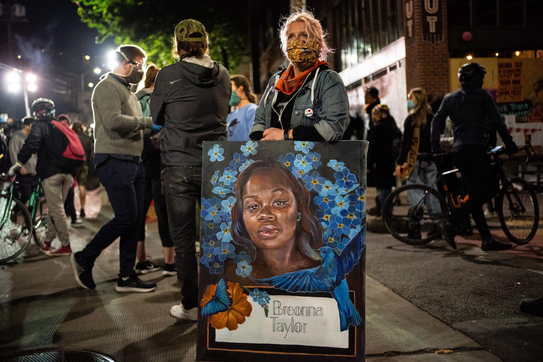 Une manifestante tient un portrait de Breonna Taylor lors d'une manifestation contre les violences policières devant la police de Seattle dans l'État de Washington, le 7 juin 2020.
