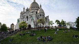 People sit on the stairs in front of the Sacre Coeur Basilica in Paris, on May 12, 2020, on the second day of France's easing of lockdown measures in place for 55 days to curb the spread of the Covid-19 pandemic.