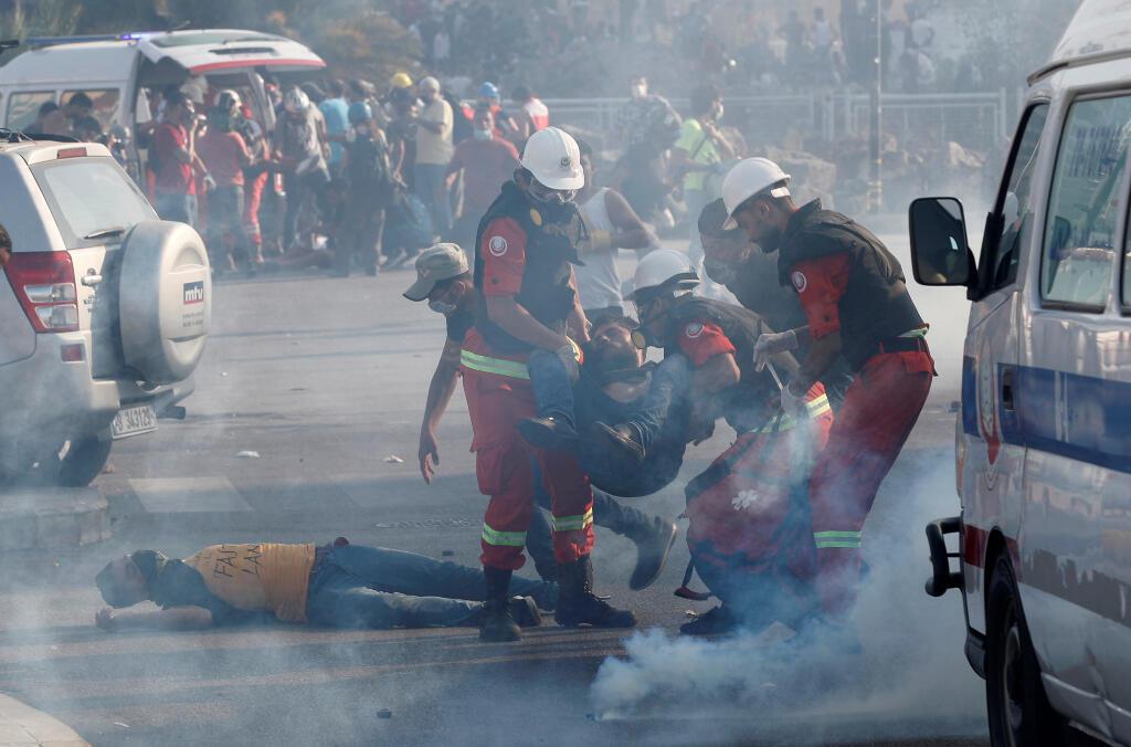 Los equipos de rescate ayudan a los manifestantes durante una protesta, luego de la explosión del martes, en Beirut, Líbano , el 8 de agosto de 2020.