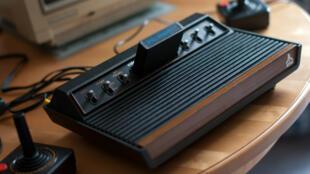 Une console Atari 2600 VCS, ses joysticks et un Commodore 1084S en arrière-plan.