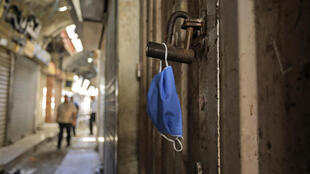A face mask hangs on the lock of a shop in Gaza City on May 22, 2020, amid the novel coronavirus pandemic crisis