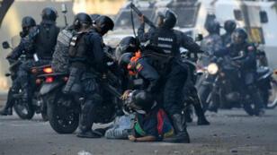 Un manifestante antigubernamental es detenido por fuerzas de seguridad durante enfrentamientos con fuerzas policiales en Caracas en conmemoración del Primero de Mayo, el 1 de mayo de 2019, después de un día de violentos enfrentamientos en las calles.