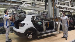 Dos operarios con mascarilla trabajan en la fábrica de automóviles Volkswagen en la ciudad española de Pamplona, el 30 de abril de 2020