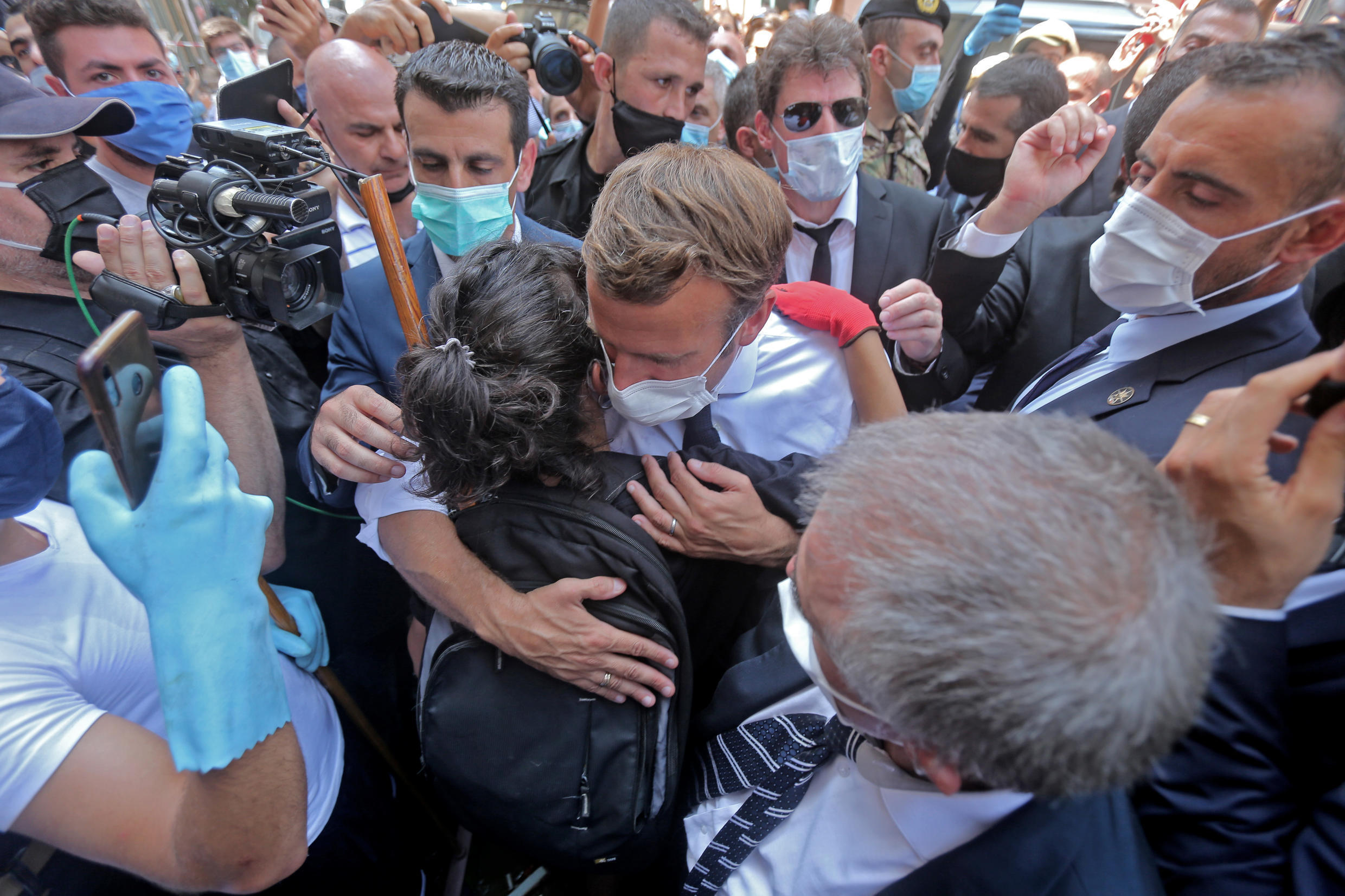 A Lebanese youth hugs French President Emmanuel Macron during his visit to the Gemmayzeh neighborhood of Beirut, which has suffered extensive damage due to Tuesday's massive explosion in the Lebanese capital, on August 6, 2020.