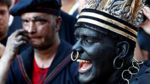 """""""The Savage"""", un intérprete blanco disfrazado de afrodescenciente, participa en el festival Ducasse d'Ath, en la ciudad occidental de Ath, Bélgica, el 25 de agosto de 2019."""