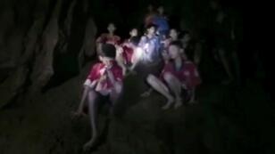 Les enfants et leur entraîneur, sains et saufs, dans la grotte où ils ont été piégés le 23 juin par la montée des eaux.