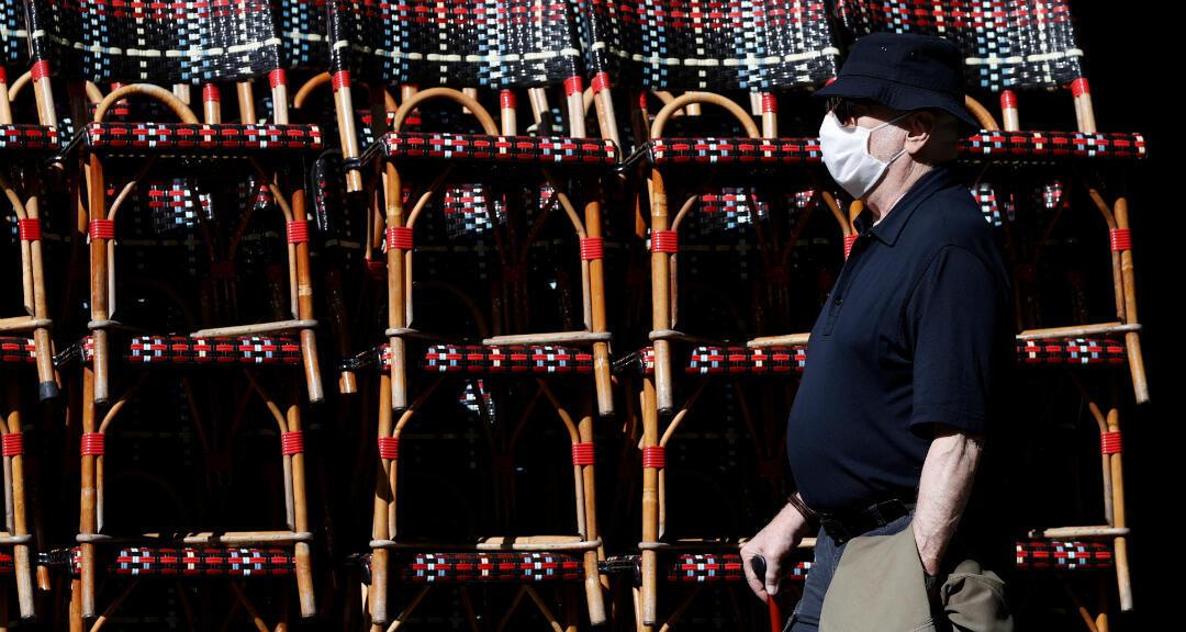 Un hombre con una mascarilla pasa por un restaurante en París, Francia, el 1 de junio de 2020.