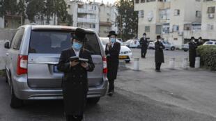 يهود من المتدينين المتشددين يضعون كمامات يصلون خارج كنيس في أشدود بجنوب إسرائيل في 16 حزيران/يونيو 2020