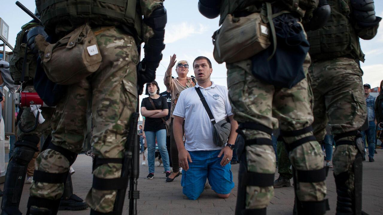 La gente habla policías cerca del lugar donde un manifestante murió durante una manifestación después de las elecciones presidenciales en Minsk, Bielorrusia, el 11 de agosto de 2020.