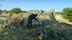 Un homme fouille en janvier 2013 parmi les ruines du mausolée d'Alfa Moya, un saint musulman, dans le cimetière de Tombouctou après sa destruction par des islamistes.