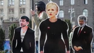 Un hombre se para junto a las figuras de cartón de tres de los candidatos presidenciales en Ucrania: Volodymyr Zelenskiy, Yulia Tymoshenko e Igor Kolomoisky. Kiev, Ucrania, 29 de marzo de 2019.