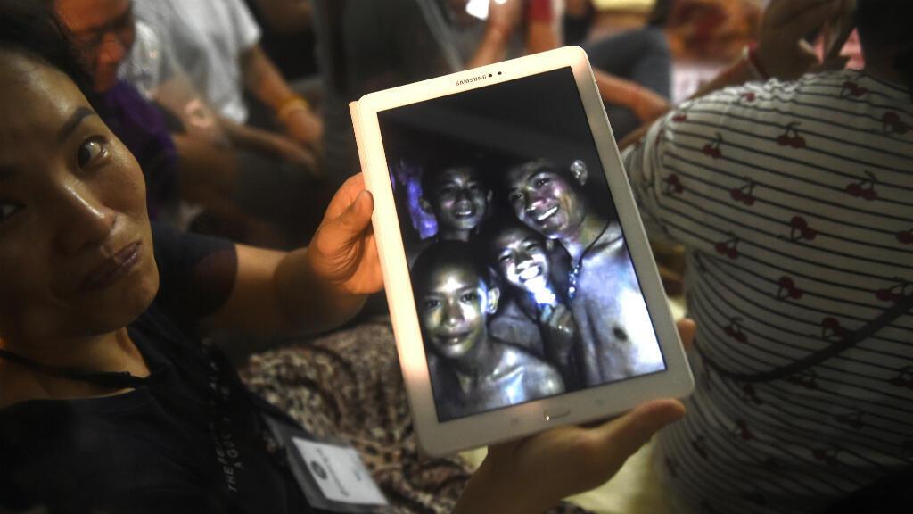 Un miembro de la familia feliz muestra la última foto de los niños desaparecidos tomada por los buzos de rescate dentro de la cueva Tham Luang cuando todos los miembros del equipo de fútbol infantil y su entrenador fueron encontrados con vida en la cueva en Khun Nam Nang Non Forest Park en el distrito de Mae Sai de Chiang Provincia de Rai el 2 de julio de 2018.