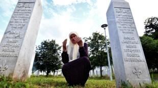 البوسنية المسلمة ميرا ديوغاز (71 عاما) الناجية من مجزرة سريبرينيتسا تصلي على أرواح أبنائها في نصب بوتوتشاري في 03 تموز/يوليو 2020