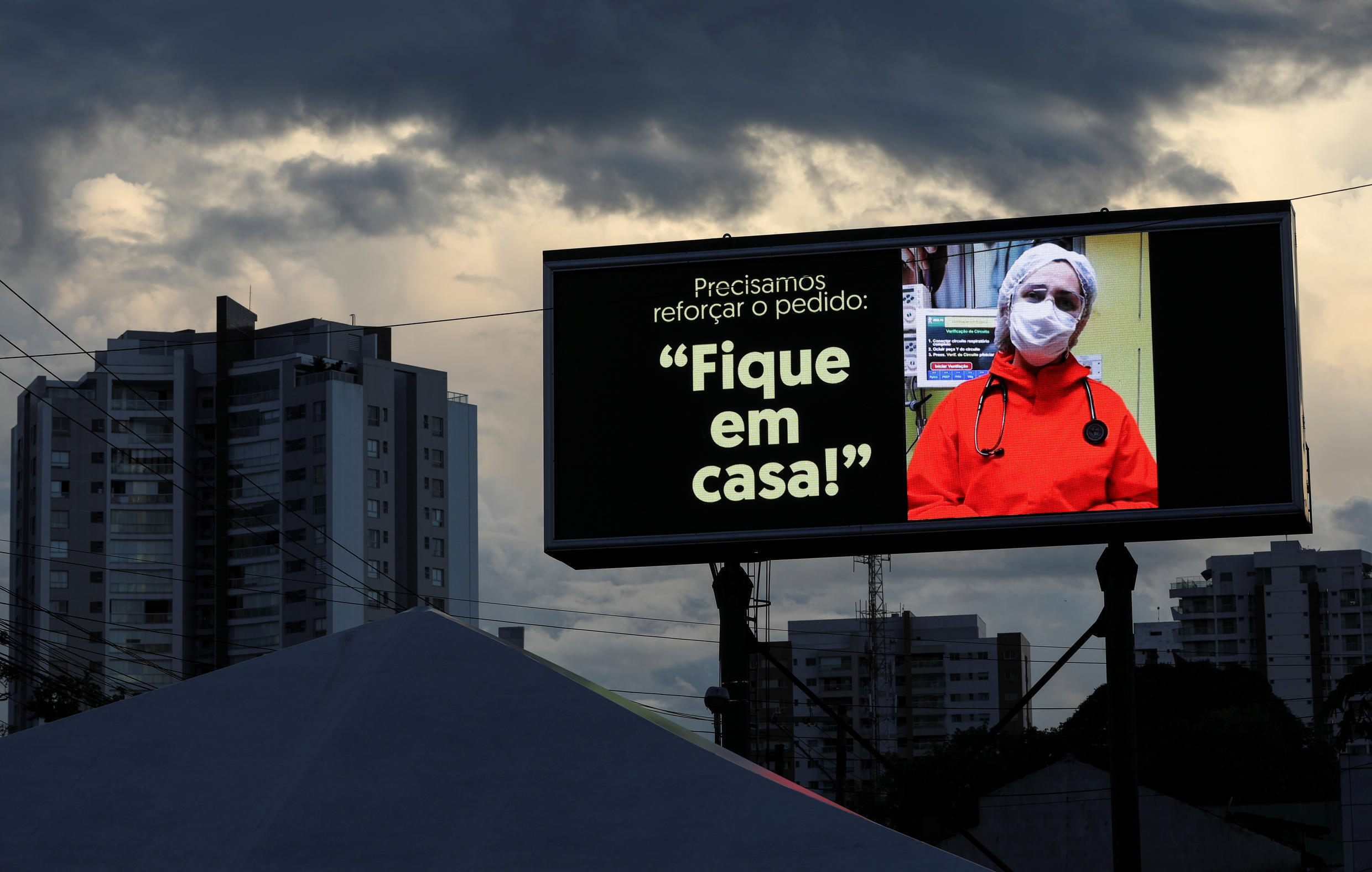 """A sign that reads """"Stay at home"""" is seen in front of the 28 de Agosto hospital during a demonstration in tribute to healthcare professionals who died from Covid-19 in Manaus, Brazil on May 16, 2020."""