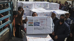 Health workers unload the first shipment boxes of Covid-19 coronavirus vaccine donated by the Indian government at Kabul airport on February 7