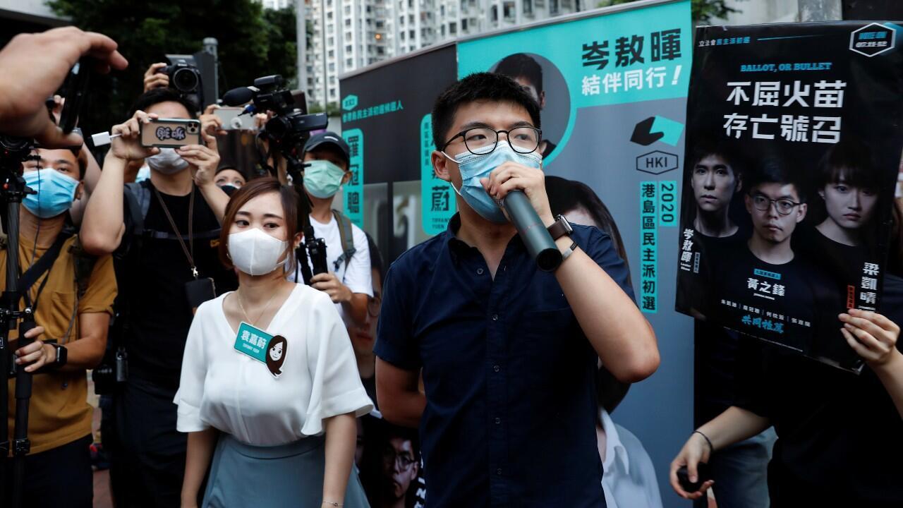 Los activistas, Tiffany Yuen Ka-wai y Joshua Wong, asisten a una campaña durante las elecciones primarias en Hong Kong