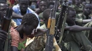 Child soldiers sit with their rifles at a disarmament, demobilisation and reintegration ceremony in Pibor, South Sudan in February 2015.