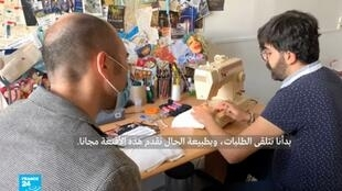 طالب في غرفته بالسكن الجامعي بصدد صنع كمامة.