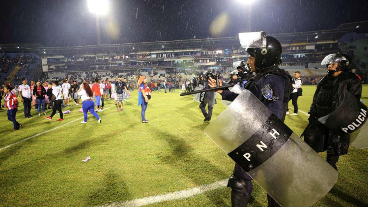 Aficionados ingresan al campo y se protegen de los gases lacrimógenos lanzados por las autoridades, debido a los disturbios a las afueras del Estadio Nacional por la cancelación del clásico entre Olimpia y Motagua. 17 de agosto de 2019.