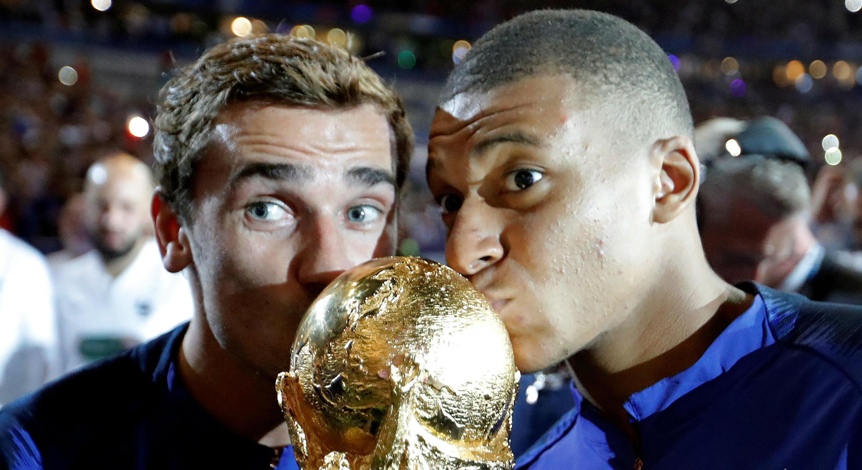 Antoine Griezmann y Kylian Mbappé besan el trofeo del Mundial de la FIFA en Moscú. 15 de julio de 2018.