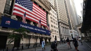 Peatones caminan fuera de la Bolsa de Nueva York el 13 de julio de 2020