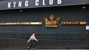 A woman wearing a mask walks in front of a closed nightclub in Seoul, South Korea on May 10, 2020.  Jung Yeon-je AFP