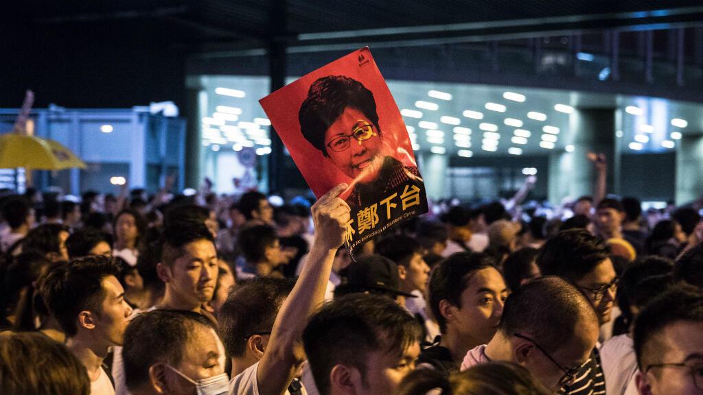 Un manifestant brandissant un portrait de Carrie Lam aux couleurs de la Chine lors de la manifestation du dimanche 9 juin, à Hong Kong.