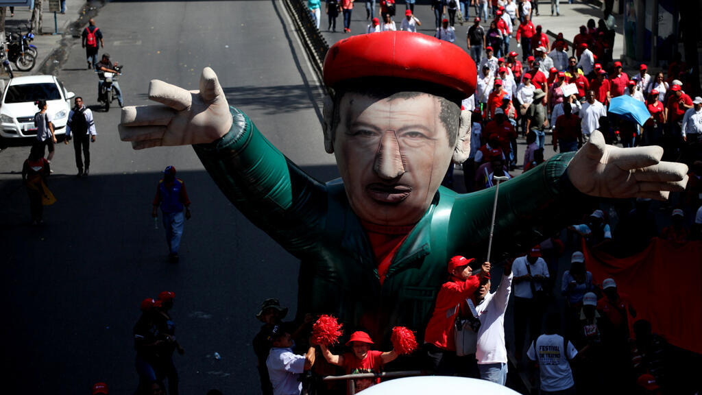 Partidarios de Nicolás Maduro llevan hoy 31 de enero un muñeco inflable gigante del fallecido presidente de Venezuela, Hugo Chávez, durante un mitin en apoyo a la petrolera estatal PDVSA en el centro de Caracas, Venezuela.