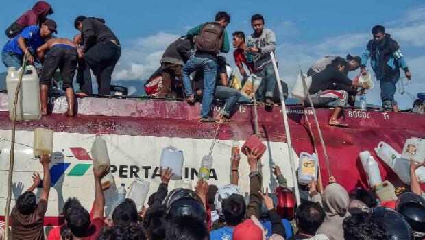 La gente busca combustible de un camión cisterna golpeado en un terremoto y tsunami en Palu, Sulawesi Central, Indonesia, 30 de septiembre de 2018.