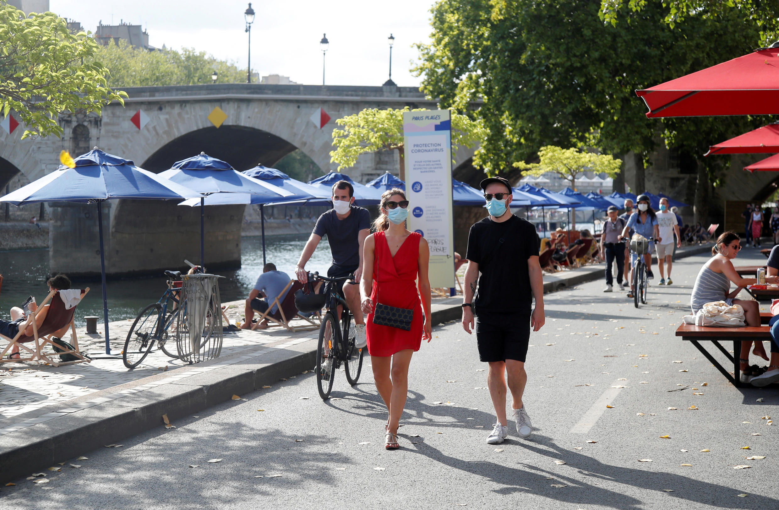 Pedestrians wearing protective face masks walk along the Seine river banks, as France reinforces mask-wearing as part of efforts to curb a resurgence of Covid-19 across the country, Paris, France, August 15, 2020.