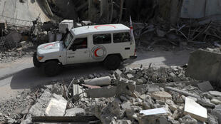 Amer Almohibany, AFP | A vehicle from a Syrian Red Crescent convoy drives through Douma in the Syrian rebel enclave of Eastern Ghouta on March 5.