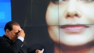 برلوسكوني خلال تسجيل برنامج تلفزيوني في روما في 2009 وتبدو صورة لزوجته فيرونيكا لاريو