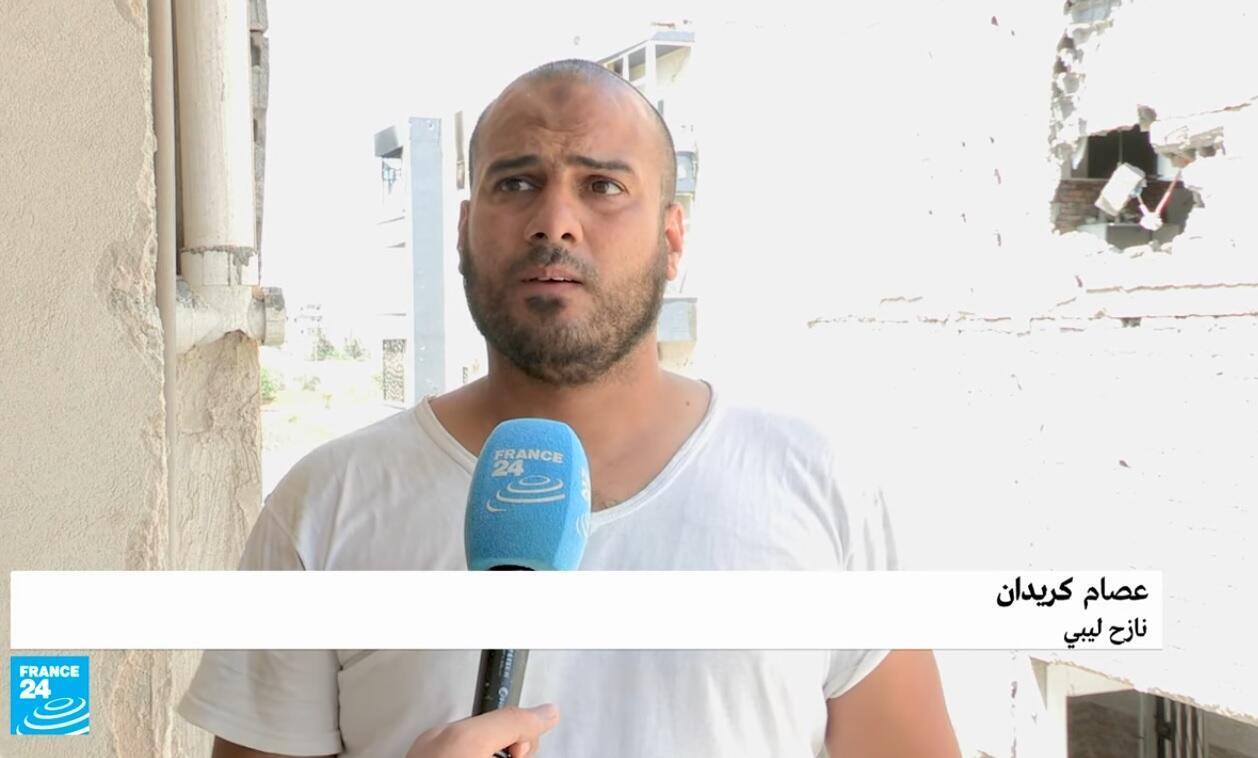 أحد النازحين بالعاصمة الليبية طرابلس لدى عودته إلى منزله وسط الدمار.
