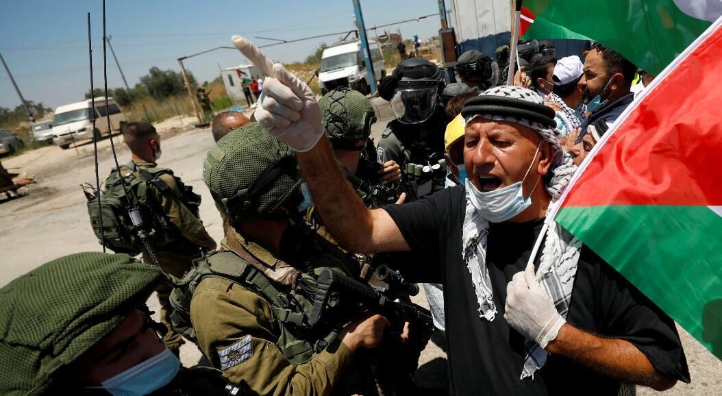 Un manifestante con la bandera de los territorios palestinos frente a las fuerzas armadas israelíes, durante una protesta contra el plan de anexión de Israel de partes de Cisjordania. En Haris, Cisjordania, el 26 de junio de 2020.