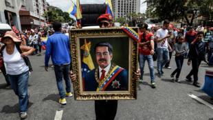 Un manifestant avec un portrait de Nicolas Maduro, le 23 mars 2019, dans les rues de Caracas.